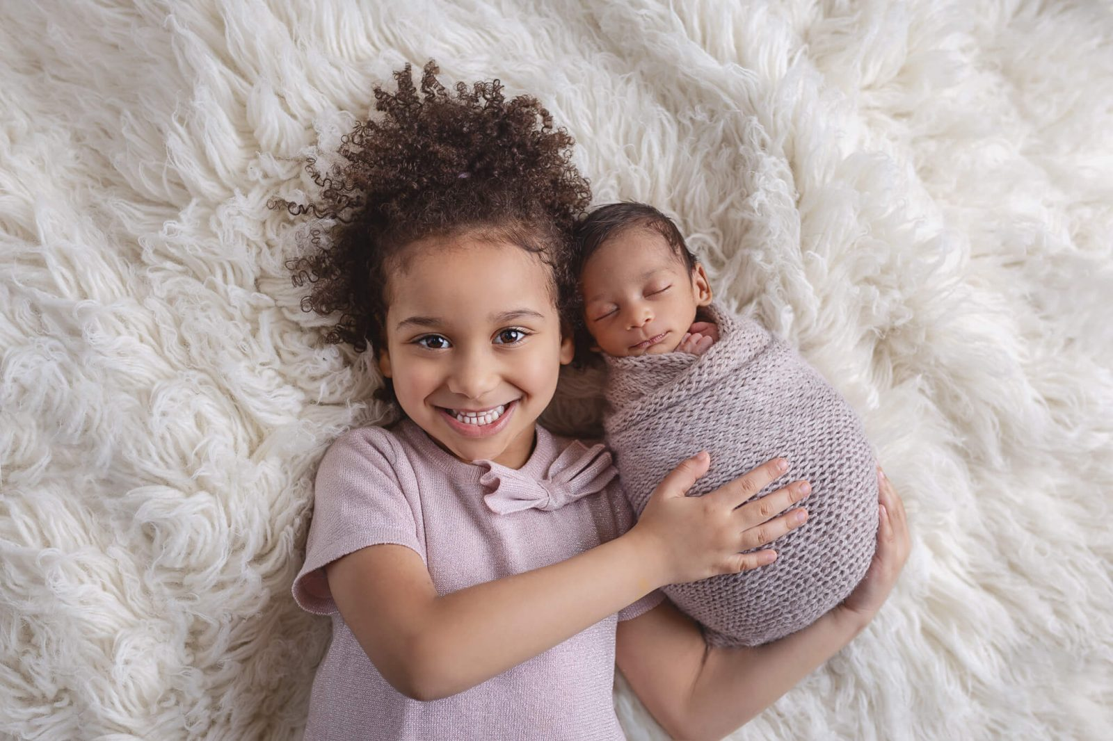 newborn with sibling on a bed